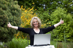 Mujer con la computadora portátil que presenta ambos pulgares para arriba Foto de archivo libre de regalías
