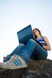 Mujer con la computadora portátil y el cielo azul Fotos de archivo libres de regalías