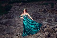 Mujer con la corona en la cabeza en el vestido largo verde que plantea la mirada a echar a un lado fotografía de archivo libre de regalías