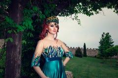 Mujer con la corona en la cabeza en el vestido largo verde que presenta mirándole cámara foto de archivo libre de regalías