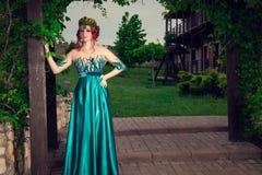 Mujer con la corona en la cabeza en el vestido largo verde que presenta mirándole cámara imágenes de archivo libres de regalías