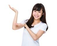 Mujer con la demostración de la mano con la muestra en blanco foto de archivo