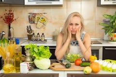 Mujer con la emoción triste en la tabla de cocina Imagen de archivo libre de regalías