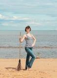 Mujer con la escoba en la playa Fotos de archivo