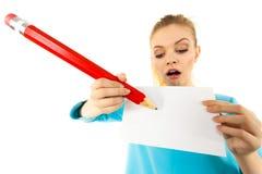 Mujer con la escritura grande del lápiz en el papel Foto de archivo