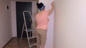 Mujer con la esquina de la pintura del cepillo metrajes
