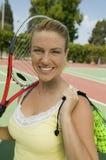 Mujer con la estafa de tenis y pelotas de tenis en el retrato del campo de tenis Foto de archivo libre de regalías