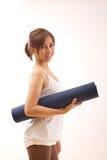 Mujer con la estera de la yoga Imagen de archivo libre de regalías