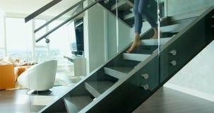 Mujer con la estera de la yoga que camina abajo en la caja 4k de la escalera almacen de video
