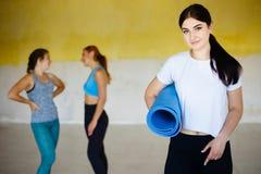 Mujer con la estera de la yoga que presenta con los amigos en gimnasio Imagenes de archivo