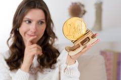 Mujer con la expresión escéptica de la cara que mira una moneda euro de oro Imagenes de archivo