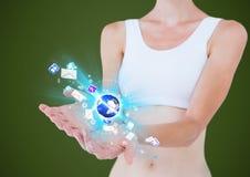mujer con la extensión de las manos de y la tierra con los iconos del uso encima Fondo verde Foto de archivo libre de regalías
