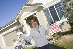Mujer con la familia que se coloca en Front Of House For Sale Foto de archivo