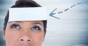 Mujer con la flecha azul que señala a la tarjeta en la cabeza contra el panel de madera azul borroso Fotografía de archivo