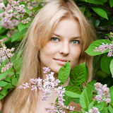 Mujer con la flor de la lila en cara Fotografía de archivo libre de regalías