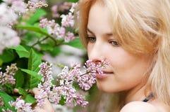 Mujer con la flor de la lila en cara Fotografía de archivo