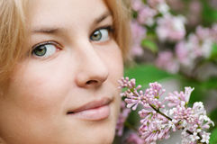 Mujer con la flor de la lila en cara Foto de archivo libre de regalías