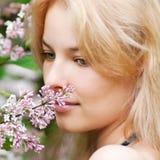 Mujer con la flor de la lila en cara Fotos de archivo libres de regalías