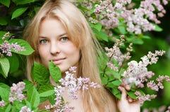 Mujer con la flor de la lila en cara Imagen de archivo libre de regalías
