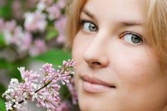 Mujer con la flor de la lila en cara Imágenes de archivo libres de regalías