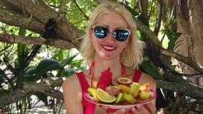 Mujer con la fruta tropical almacen de video