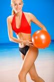 Mujer con la gimnasia-bola en la playa Foto de archivo libre de regalías