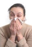 Mujer con la gripe fuerte que sopla su nariz Fotografía de archivo
