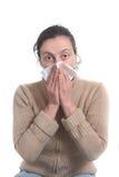 Mujer con la gripe fuerte que sopla su nariz Imagen de archivo libre de regalías