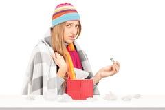 Mujer con la gripe que sostiene un termómetro, rectángulo con los tisssues de papel encendido Imagenes de archivo