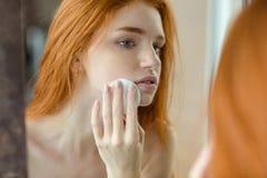 Mujer con la guata que mira su reflexión en espejo Foto de archivo libre de regalías