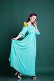 Mujer con la guirnalda de flores en vestido azul largo Imágenes de archivo libres de regalías