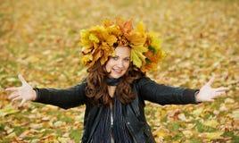 Mujer con la guirnalda del arce en el otoño al aire libre Fotos de archivo
