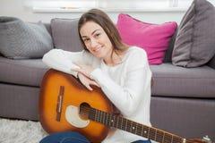 Mujer con la guitarra acústica Imagen de archivo libre de regalías