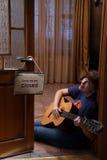 Mujer con la guitarra que se sienta en el piso en el café Imagen de archivo libre de regalías