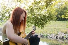 Mujer con la guitarra que se sienta en un árbol Imagenes de archivo