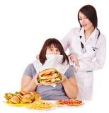 Mujer con la hamburguesa y el doctor. Imagen de archivo libre de regalías