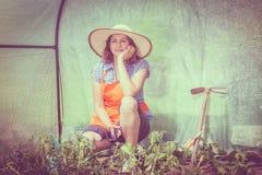 Mujer con la herramienta que cultiva un huerto que trabaja en invernadero Foto de archivo libre de regalías