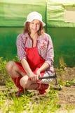 Mujer con la herramienta que cultiva un huerto que trabaja en jardín Foto de archivo
