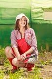 Mujer con la herramienta que cultiva un huerto que trabaja en jardín Imagen de archivo libre de regalías