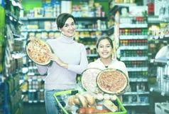 Mujer con la hija adolescente que busca para la pizza Imagen de archivo libre de regalías