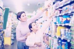 Mujer con la hija adolescente que busca para las galletas Fotos de archivo libres de regalías