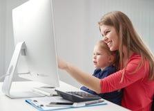 Mujer con la hija en el ordenador Foto de archivo libre de regalías