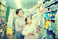 Mujer con la hija que elige las galletas en supermercado Foto de archivo libre de regalías
