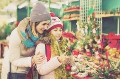 Mujer con la hija que mira la decoración floral el fai de Cristmas Foto de archivo
