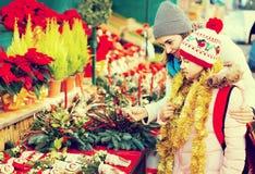 Mujer con la hija que mira la decoración floral el fai de Cristmas Imagen de archivo