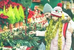 Mujer con la hija que mira la decoración floral el fai de Cristmas Fotos de archivo