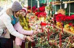 Mujer con la hija que mira la decoración floral el fai de Cristmas Foto de archivo libre de regalías