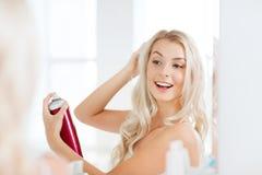 Mujer con la laca que diseña su pelo en el cuarto de baño Imagenes de archivo