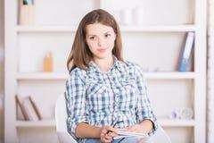 Mujer con la libreta que piensa en oficina Imagenes de archivo