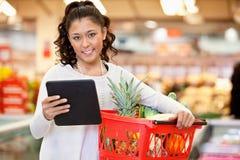 Mujer con la lista de compras de la PC de la tablilla fotos de archivo